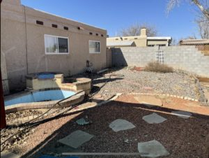 A photo of my New Mexico backyard garden space. There is an empty blue pond to the left and the rest is mostly a rock covered ground, a stucco house, and a grey concrete wall.